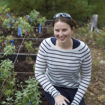 Caitlin in striped shirt next to experimental garden