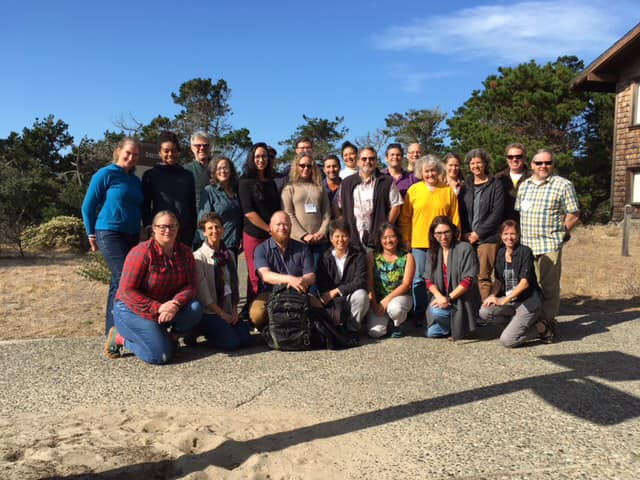 Posed group photo of workshop participants outside with blue sky