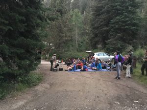 A park ranger delivers a bat program to a group of visitors sitting in a dirt road.