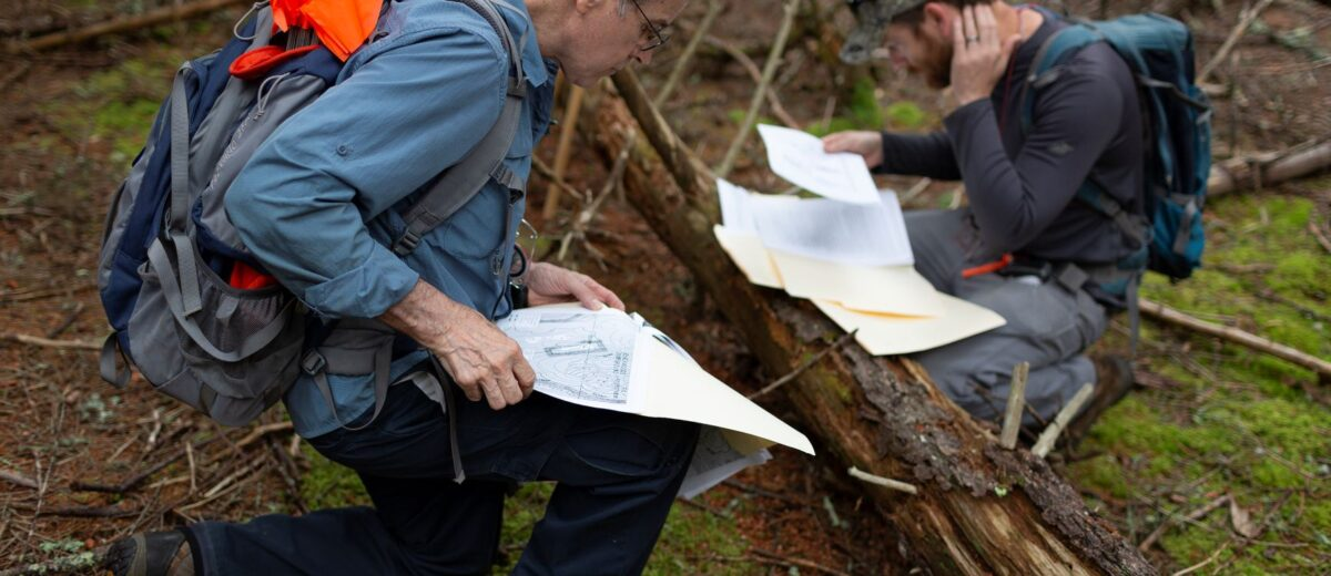 Two people wearing backpacks pause at a log in the woods to review maps